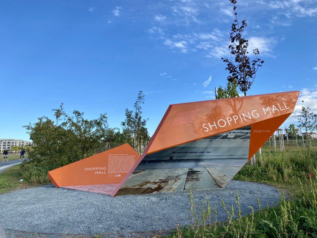 Eine der auffallenden, orangenen Stelen: Infotafel über die ehemalige Shoppingmall