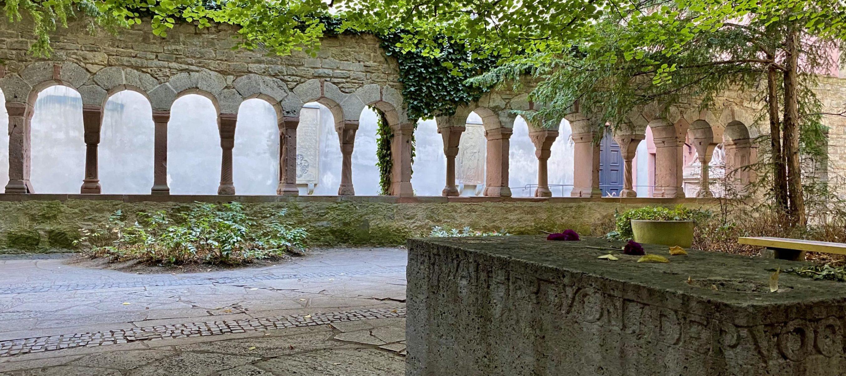 Der Grabstein von Walther von der Vogelweide mit dem Nordflügel des Kreuzgangs im Hintergrund